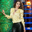 Attractive brunette woman with long hair in elegant yellow blouse and black leather pants standing near bright green wall in a nightclub. Gorgeous model posing in a modern emerald textured scenery — Stock Photo #44953891