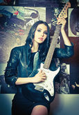 Beautiful brunette with electric guitar. Rocker young woman holding a guitar indoor. Female musician wearing a black jacket and short skirt posing with a guitar — Stock Photo