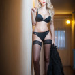 Attractive sexy blonde in black lingerie posing provocatively indoor. Portrait of sensual woman wearing black lingerie in classic boudoir scene. Woman with long hair and black stockings against a wall — Stock Photo