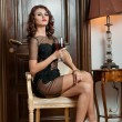 Charming young brunette in transparent lace black dress with glass of wine sitting. Beautiful sexy girl on high heels holding a glass, vintage scenery. Gorgeous sensual long hair woman posing. — Stock Photo