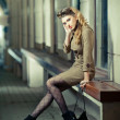 Attractive blonde girl wearing short dress and high heels - urban scene. Fashion model with long sexy legs sitting on bench thinking. Elegant woman wearing outfit with Russian influence posing relaxed — Stock Photo #45096915