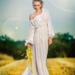 Young woman with long white dress standing on a wheat field. Portrait of girl outdoor. Romantic young woman posing on clean blue sky. Attractive woman in white dress in yellow wheat field at sunrise. — Stock Photo #45353199