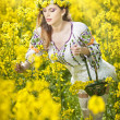 Young girl wearing Romanian traditional blouse holding a basket in canola field, outdoor shot. Portrait of beautiful blonde with blue eyes smiling and enjoying the bright yellow flowers of rapeseed — Stock Photo