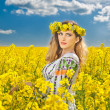 Young girl wearing Romanian traditional blouse posing in canola field with cloudy sky in background, outdoor shot. Portrait of beautiful blonde with blue eyes smiling in rapeseed field — Stock Photo #45374607