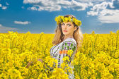 Young girl wearing Romanian traditional blouse posing in canola field with cloudy sky in background, outdoor shot. Portrait of beautiful blonde with blue eyes smiling in rapeseed field — Stock Photo