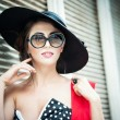 Attractive brunette girl with black hat, red scarf and sunglasses posing outdoor. Beautiful fashionable young woman with modern accessories, urban shot. Gorgeous brunette with large black hat smiling. — Stock Photo