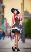 Fashionable lady wearing elegant dress, black hat and red scarf posing outdoor in urban scenery. Full length portrait of young beautiful elegant woman posing in summer city style. Street shot. — Stock Photo
