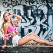Attractive blonde girl posing fashion sitting on the street ledge. Young fair hair woman with shorts in front of a graffiti wall. Beautiful long hair female with pink bra, urban shot — Stock Photo #45647611