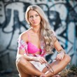 Attractive blonde girl posing fashion sitting on the street ledge. Young fair hair woman with shorts in front of a graffiti wall. Beautiful long hair female with pink bra, urban shot — Stock Photo #45647645