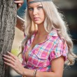 Beautiful blonde female in summer park near a tree. Young pretty woman with pink checked shirt posing outdoor. Attractive fair hair girl with flower power look spending time in park. — Stock Photo #45647655