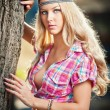Beautiful blonde female in summer park near a tree. Young pretty woman with pink checked shirt posing outdoor. Attractive fair hair girl with flower power look spending time in park. — Stock Photo #45647669