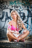 Attractive blonde girl posing fashion sitting on the street ledge. Young fair hair woman with shorts in front of a graffiti wall. Beautiful long hair female with pink bra, urban shot — Stock Photo