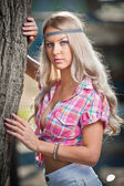 Beautiful blonde female in summer park near a tree. Young pretty woman with pink checked shirt posing outdoor. Attractive fair hair girl with flower power look spending time in park. — Stock Photo