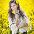 Pretty long hair girl wearing white blouse posing holding a basket in canola field, outdoor shot. Portrait of beautiful brunette with bright yellow flowers in hair smiling and enjoying the rapeseed — Stock Photo #45666081