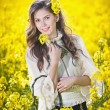 Pretty long hair girl wearing white blouse posing holding a basket in canola field, outdoor shot. Portrait of beautiful brunette with bright yellow flowers in hair smiling and enjoying the rapeseed — Stock Photo