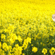 Young girl wearing Romanian traditional blouse and hat posing in canola field, outdoor shot. Lady photographer shooting beautiful blonde smiling and enjoying the bright yellow flowers of rapeseed — Stock Photo #45666093