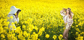 Young girl wearing Romanian traditional blouse and hat posing in canola field, outdoor shot. Lady photographer shooting beautiful blonde smiling and enjoying the bright yellow flowers of rapeseed — Stock Photo