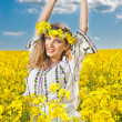 Young girl wearing Romanian traditional blouse posing in canola field with cloudy sky in background, outdoor shot. Portrait of beautiful blonde with flowers wreath smiling in rapeseed field — Stock Photo #45693733