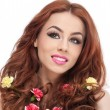 Portrait of beautiful girl in studio with yellow and red carnations in her curly hair. Sexy young woman with red hair colored flowers isolated. Creative hairstyle and makeup, fashion photo studio shot — Zdjęcie stockowe
