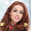 Portrait of beautiful girl in studio with yellow and red carnations in her curly hair. Sexy young woman with red hair colored flowers isolated. Creative hairstyle and makeup, fashion photo studio shot — Photo