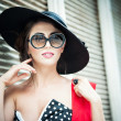 Attractive brunette girl with black hat, red scarf and sunglasses posing outdoor. Beautiful fashionable young woman with modern accessories, urban shot. Gorgeous brunette with large black hat smiling. — Stock Photo #45759973