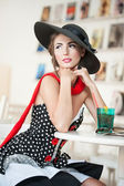 Fashionable attractive lady with black hat and red scarf sitting on chair in restaurant, indoor shot. Young woman posing in elegant scenery. Art photo of elegant sensual woman, vintage style — Stock Photo