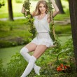 Beautiful young woman in short white dress posing in a leaves decorated swing in garden. Gorgeous fair hair girl swinging in park, outdoor shot. Attractive blonde with long legs sitting on cradle — Stock Photo #45775561