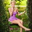 Beautiful young woman in pink short dress dreaming in a leaves decorated swing between two trees. Gorgeous fair hair girl posing in garden, outdoor shot. Attractive blonde swinging on leafy swing — Stock Photo #45775563