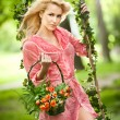 Beautiful young woman in pink short dress holding a basket with flowers in a leaves decorated swing. Gorgeous fair hair girl posing in garden, outdoor shot. Attractive blonde swinging on leafy swing — Stock Photo