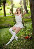 Beautiful young woman in short white dress posing in a leaves decorated swing in garden. Gorgeous fair hair girl swinging in park, outdoor shot. Attractive blonde with long legs sitting on cradle — Stock Photo