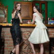 Two beautiful brunette ladies in elegant black and white lace dresses posing in vintage scenery. Young sensual fashionable women on high heels in luxurious interior with lighting chandelier. — Stock Photo #46125445