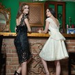 Two beautiful brunette ladies in elegant black and white lace dresses posing in vintage scenery. Young sensual fashionable women on high heels in luxurious interior with lighting chandelier. — Stock Photo