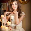 Beautiful sexy woman in white lace dress in vintage scenery with candles. Portrait of long hair brunette girl posing in luxury indoor. Attractive young fashionable female with creative makeup. — Stock Photo