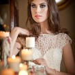 Beautiful sexy woman in white lace dress in vintage scenery with candles. Portrait of long hair brunette girl posing in luxury indoor. Attractive young fashionable female with creative makeup. — Stock Photo #46125473