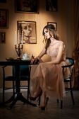 Young beautiful brunette woman in elegant lace dress sitting near a table with candlestick. Long hair attractive girl in luxurious classic interior. Seductive female in vintage scenery, indoor — Stock Photo