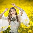 Young girl wearing elegant white blouse posing in canola field, outdoor shot. Portrait of beautiful long hair brunette with large transparent sleeves in bright yellow rapeseed field, spring scenery — Stock Photo #46149857