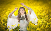 Young girl wearing elegant white blouse posing in canola field, outdoor shot. Portrait of beautiful long hair brunette with large transparent sleeves in bright yellow rapeseed field, spring scenery — Stock Photo