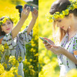 Young girl wearing Romanian traditional blouse taking selfie in canola field, outdoor shot. Portrait of beautiful blonde with flowers wreath holding her mobile in bright yellow rapeseed field — Stock Photo #46150791
