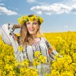 Young girl wearing Romanian traditional blouse posing in canola field with cloudy sky in background, outdoor shot. Portrait of beautiful blonde with flowers wreath smiling in rapeseed field — Stock Photo #46154211