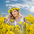 Young girl wearing Romanian traditional blouse posing in canola field with cloudy sky in background, outdoor shot. Portrait of beautiful blonde with flowers wreath smiling in rapeseed field — Stock Photo #46154213