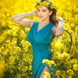 Fashion beautiful young woman in blue dress and yellow flowers wreath posing outdoor in canola field. Attractive long hair blonde girl with elegant dress smiling in rapeseed field in bright sunny day. — Stock Photo