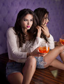 Beautiful brunette girl in denim shorts and white blouse posing on lilac textured background holding a orange drink glass in her hand. Young sensual woman siting alone in a modern night club. — Stock Photo