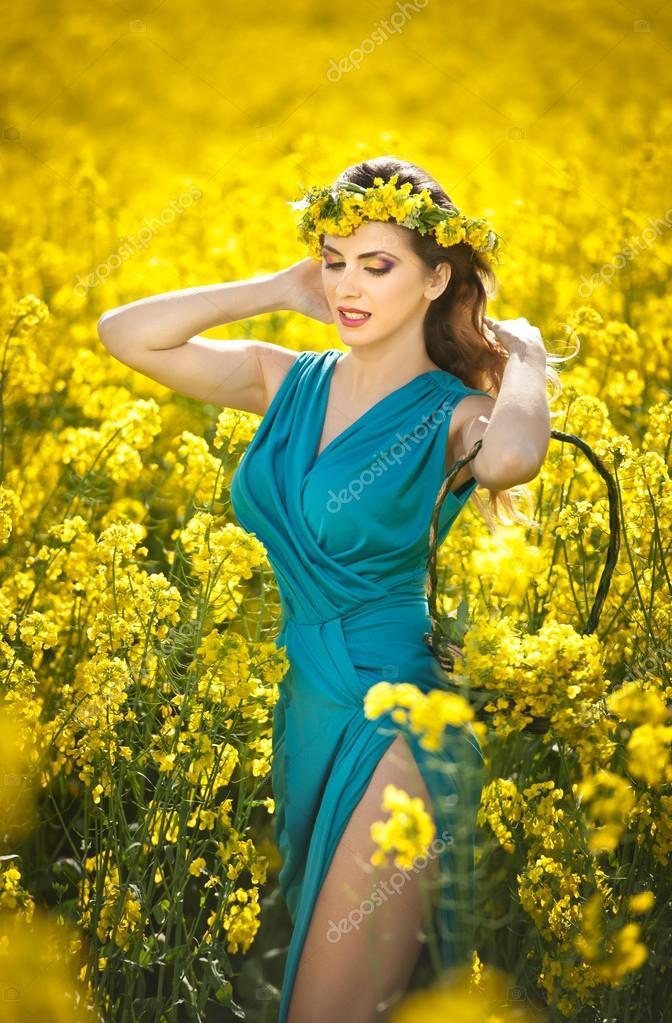 belle jeune femme en robe bleue et pose de couronne de fleurs jaunes en plein air dans le champ. Black Bedroom Furniture Sets. Home Design Ideas
