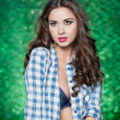 Fashion caucasian model posing indoor on bright green textured background. Sexy brunette with white and blue checkered shirt. Attractive long hair woman with unbuttoned shirt exposing nice chest. — Stock Photo #47708921
