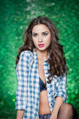 Fashion caucasian model posing indoor on bright green textured background. Sexy brunette with white and blue checkered shirt. Attractive long hair woman with unbuttoned shirt exposing nice chest. — Stock Photo