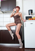 Attractive sexy woman in shirt and socks drinking milk in kitchen. Portrait of sensual girl with long legs wearing cosy comfortable clothes in modern kitchen holding a glass with milk. Indoor shot. — Stock Photo