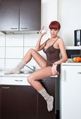 Attractive sexy woman in shirt and socks drinking milk in kitchen. Portrait of sensual girl with long legs wearing cosy comfortable clothes in modern kitchen holding a glass with milk. Indoor shot. — Foto de Stock
