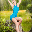 Portrait of young beautiful blonde woman wearing blue dress posing on a stump in a green forest. Fashionable sexy attractive girl sitting on hub in sunny day. Gorgeous fair hair female in garden. — Stock Photo #48379491