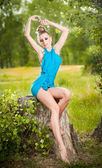 Portrait of young beautiful blonde woman wearing blue dress posing on a stump in a green forest. Fashionable sexy attractive girl sitting on hub in sunny day. Gorgeous fair hair female in garden. — Stock Photo