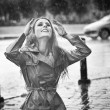 Beautiful woman wearing a coat posing in the rain. Happy long hair girl enjoying the rain drops in the park, outdoor shot. Attractive female relaxing in a rainy day. Black and white photo — Stok fotoğraf #48399705
